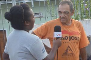 Uma jovem segura um microfone sinalizado sendo da TVQ durante entrevista com morador do bairro