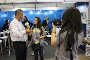 Na imagem vemos uma jovem segurando uma câmera e a outra um microfone na direção do entrevistado