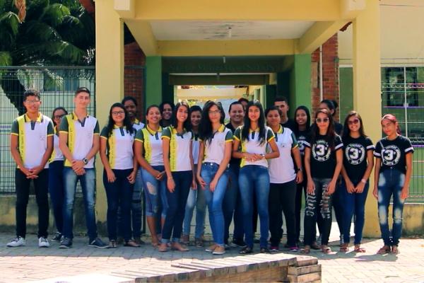 Um grupo de trinta alunos, em uniforme escolar, posam na frente de uma escola.