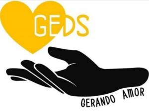 Logotipo do projeto GEDS. Na parte superior da imagem, há o desenho de um coração amarelo, com as letras GE (em branco) dentro, e logo ao lado e fora do desenho, as letras DS em amarelo. O coração está sendo amparado por uma mão preta e, embaixo dela está escrito Gerando Amor.