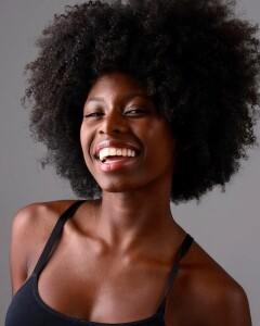 Foto de uma jovem negra sorrindo para a câmera. Ela está de cabelo solto e usa uma blusinha regata preta.