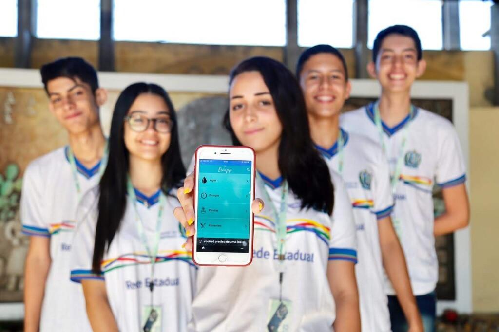 Foto de 5 estudantes enfileirados. Em primeiro plano, há uma jovem segurando um celular apontado para a câmera com uma imagem do aplicativo EcoApp na tela. Todos os jovens estão sorrindo e usando um uniforme com camiseta branca com golas e mangas azuis e linhas coloridas no centro.