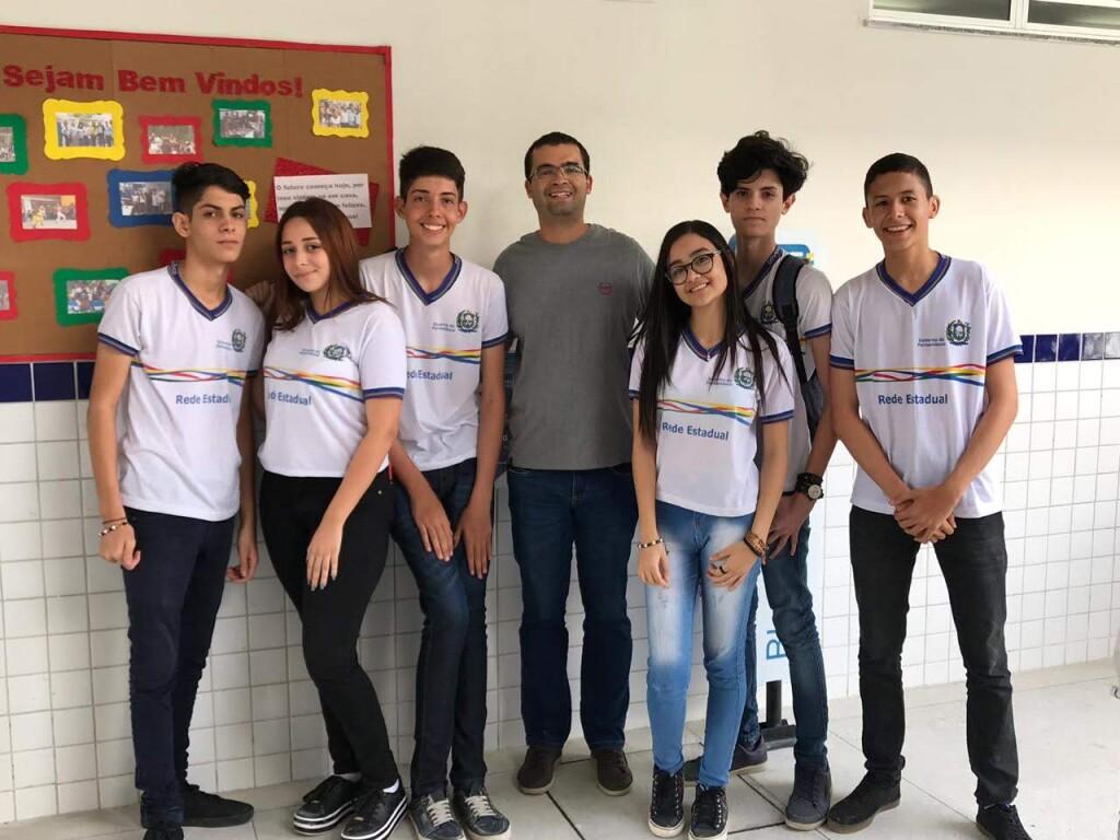 Foto com 7 pessoas em pé sorrindo para a câmera. À esquerda, há 3 jovens alunos com uniforme da escola. No centro, há um homem de camisa cinza e óculos e, à sua direita, há mais três jovens com uniforme da escola.