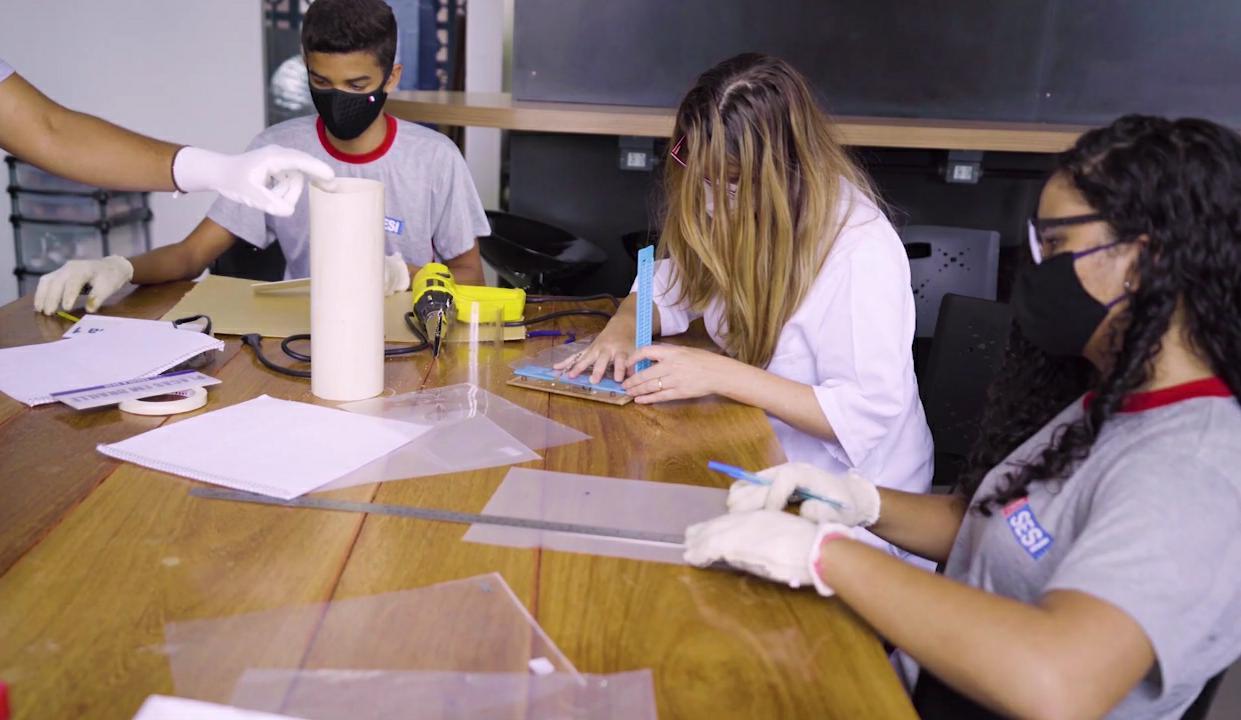 Dois estudantes e uma professora confeccionam as placas