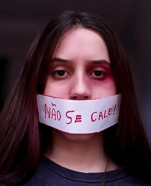 """Fotografia de uma jovem com uma faixa branca tampando sua boca. Nela está escrito, em vermelho, """"Não se cale!"""""""