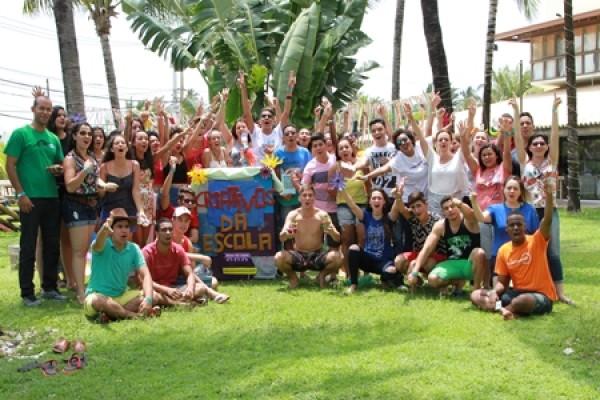 Foto de um grupo de pessoas posando em um gramado, algumas seguram a bandeira do Criativos da Escola