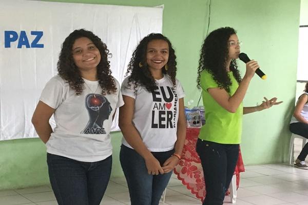 Três garotas de cabelo crespo estão de pé em uma sala de paredes verdes