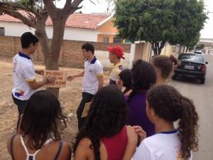 """Jovens espalham placas com a frase """"Proibido jogar lixo""""."""