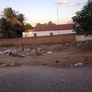 Vários sacos de lixo são vistos em um grande terreno.