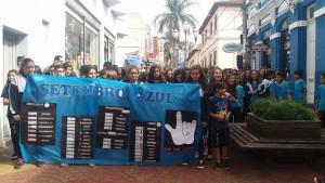 """estudantes andam na rua em passeata de conscientização com cartazes sobre """"setembro azul"""""""