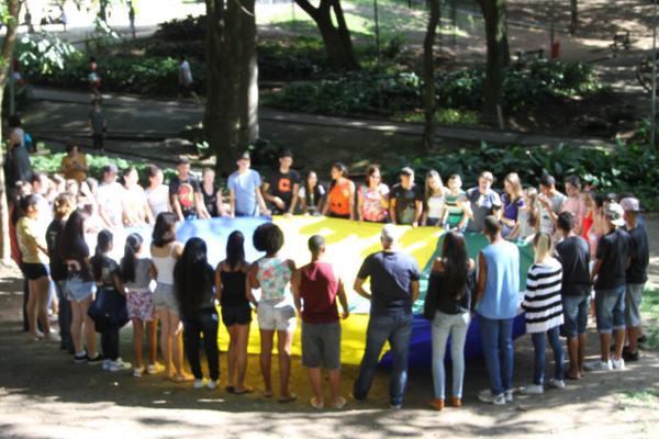Foto de um grupo de cerca de 50 pessoas segurando um tecido amarelo, formando uma grande roda