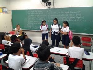 três-meninas-falam-à-frente-da-sala