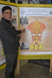 Nei -D'Ogum-sendo-apontado-por-homem-branco-em-cartaz