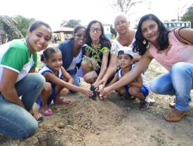 crianças_e_adultos_agachados_e_plantando_uma_muda