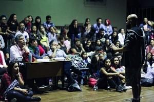 professor_dando_aula_para_dezenas_de_jovens_sentados_em_frente_a_ele