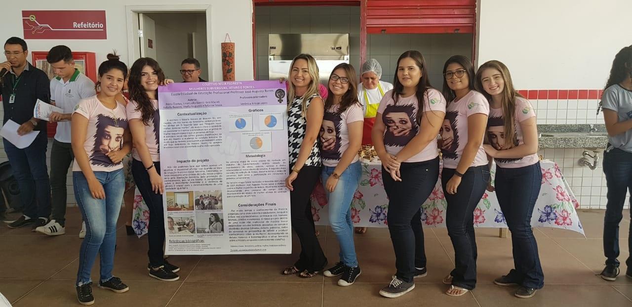 Estudantes e professora posam com banner do projeto.