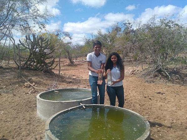 Alunos mostram processo de filtragem de água em frente a cisterna