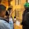 Dois adolescentes entrevistam um homem. Um segura uma câmera e o outro um microfone na direção do entrevistado