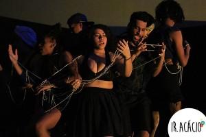 Alunos vestidos de preto se entrelaçam em uma corda durante apresentação artística
