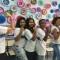 Cerca de seis estudantes erguem os braços e fazem o símbolo da força feminina