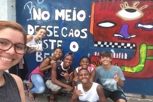 Vários alunos tiram foto em frente a um painel no páteo da escola