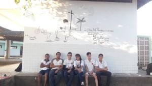 Estudantes em frente ao painel que pintaram na escola
