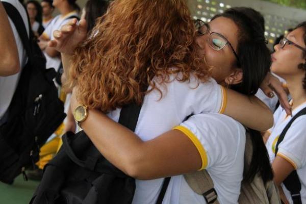 Duas meninas estão se abraçando vestidas com camisetas de uniforme de escola