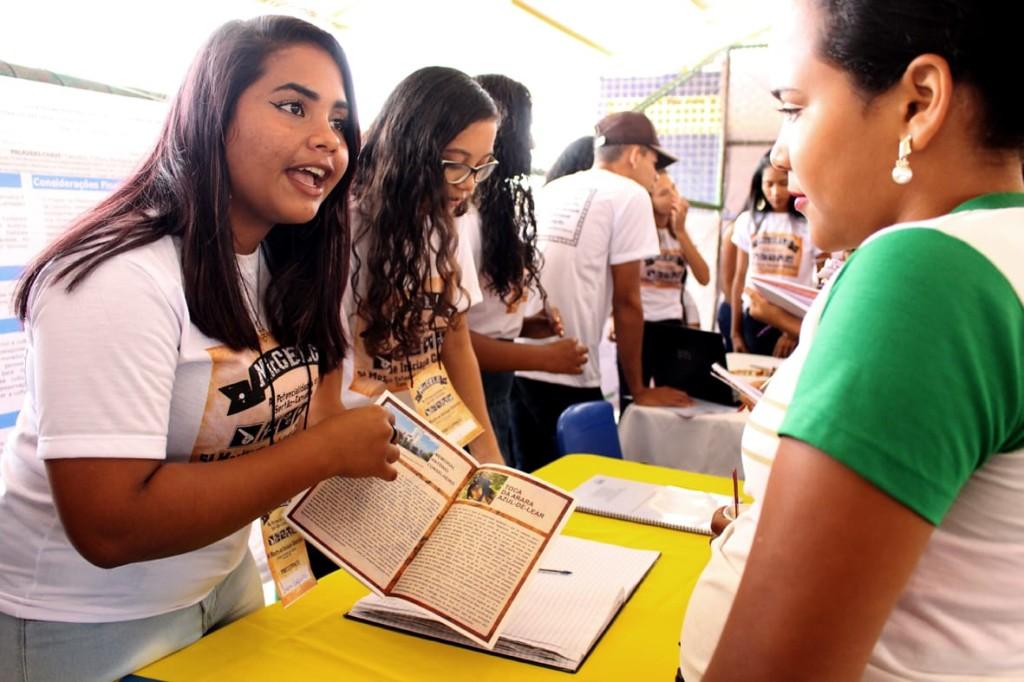 """Uma jovem mostra o """"Guia do Patrimônio Histórico e Cultural de Canudos"""", uma de cada lado de uma mesa. Ao fundo, seis outros jovens conversam entre si com cadernos e canetas."""
