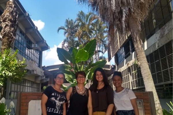 Três meninas e uma mulher sorriem posando para a foto em um espaço ao ar livre