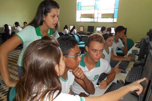 Quatro estudantes estão apontando para um computador em uma sala com outros estudantes