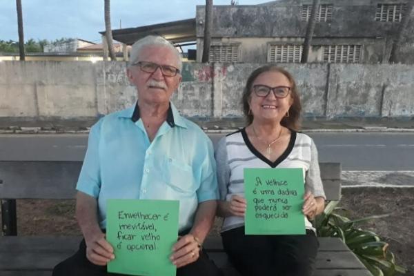 Um senhor e uma senhora seguram duas folhas verdes de papel