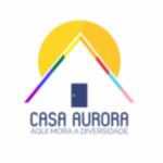 """Logotipo que imita o telhado de uma casa. As telhas são coloridas. Ao fundo, há o desenho de um sol amarelo. Abaixo do telhado, há uma porta azul. No centro, está escrito CASA AURORA em azul marinho seguido por """"Aqui mora a diversidade"""" com letras menores."""
