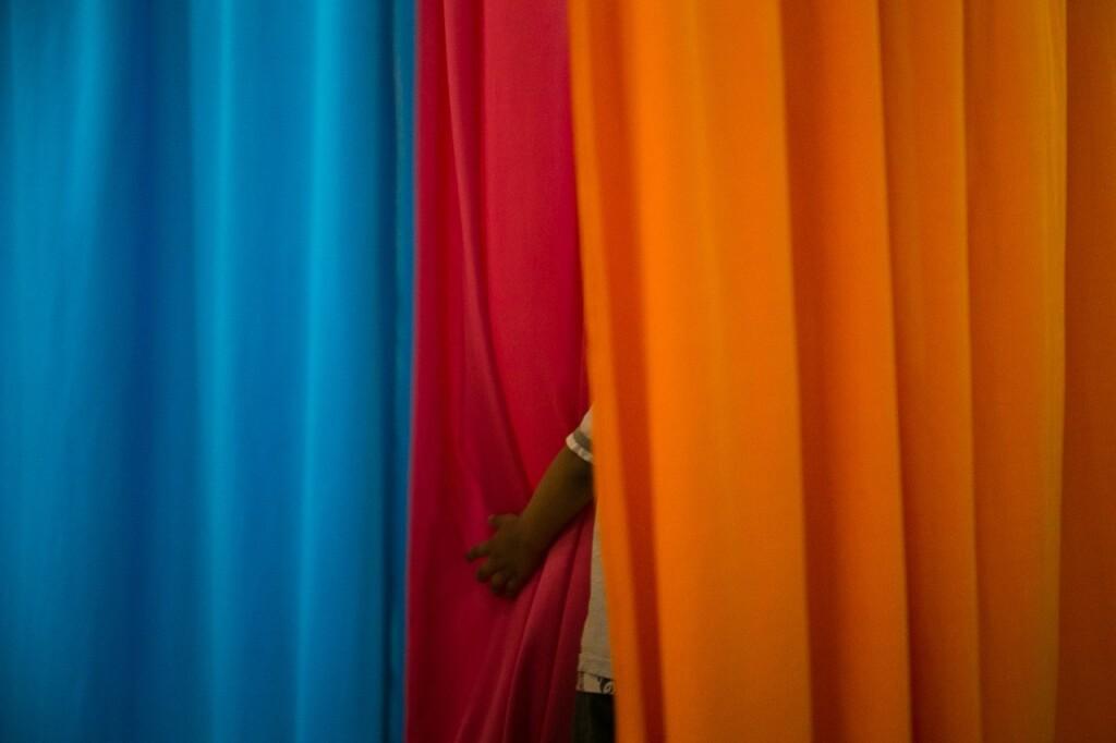Criança se esconde atrás de tecidos coloridos. - Foto: Nicolas Neves dos Santos