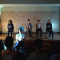 Em um palco, quatro jovens estão sentados lado a lado em cadeiras escolares. A frente do palco, outra jovem senta em outra cadeira igual a dos demais.