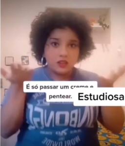 """Frame de um vídeo de uma jovem que está vestida com uma camiseta azul. Ela está falando para a câmera e na frente dela há caixas de texto, em segundo plano: """"É só passar um creme e pentear"""" e em primeiro plano e letras maiores está escrito Estudiosa"""
