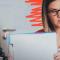 Foto de uma mulher segurando um bloco de papel. Ela usa oculos e está olhando para o lado. À esquerda da foto, há uma câmera em um tripé.