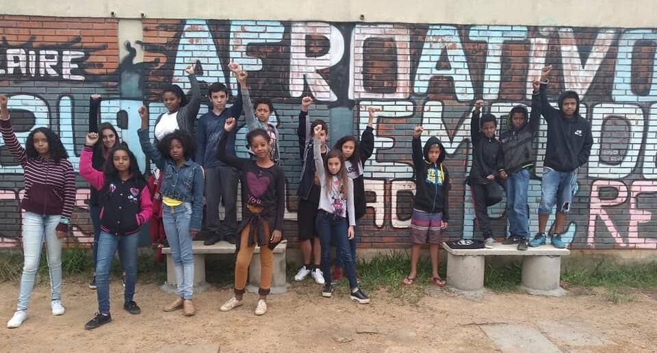 Foto onde há 15 alunos posando em uma área externa na frente de um muro onde se lê AFROATIVOS. Os alunos estão em pé, um ao lado do outro e de punhos cerrados.