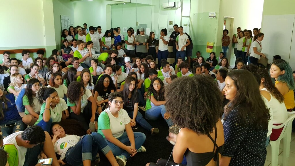 Foto de uma palestra. O quadro pega a plateia olhando para o palco: há por volta de 100 jovens com uniforme participando do evento. No palco, e de costas para a câmera, há jovens sentadas falando para a plateia.
