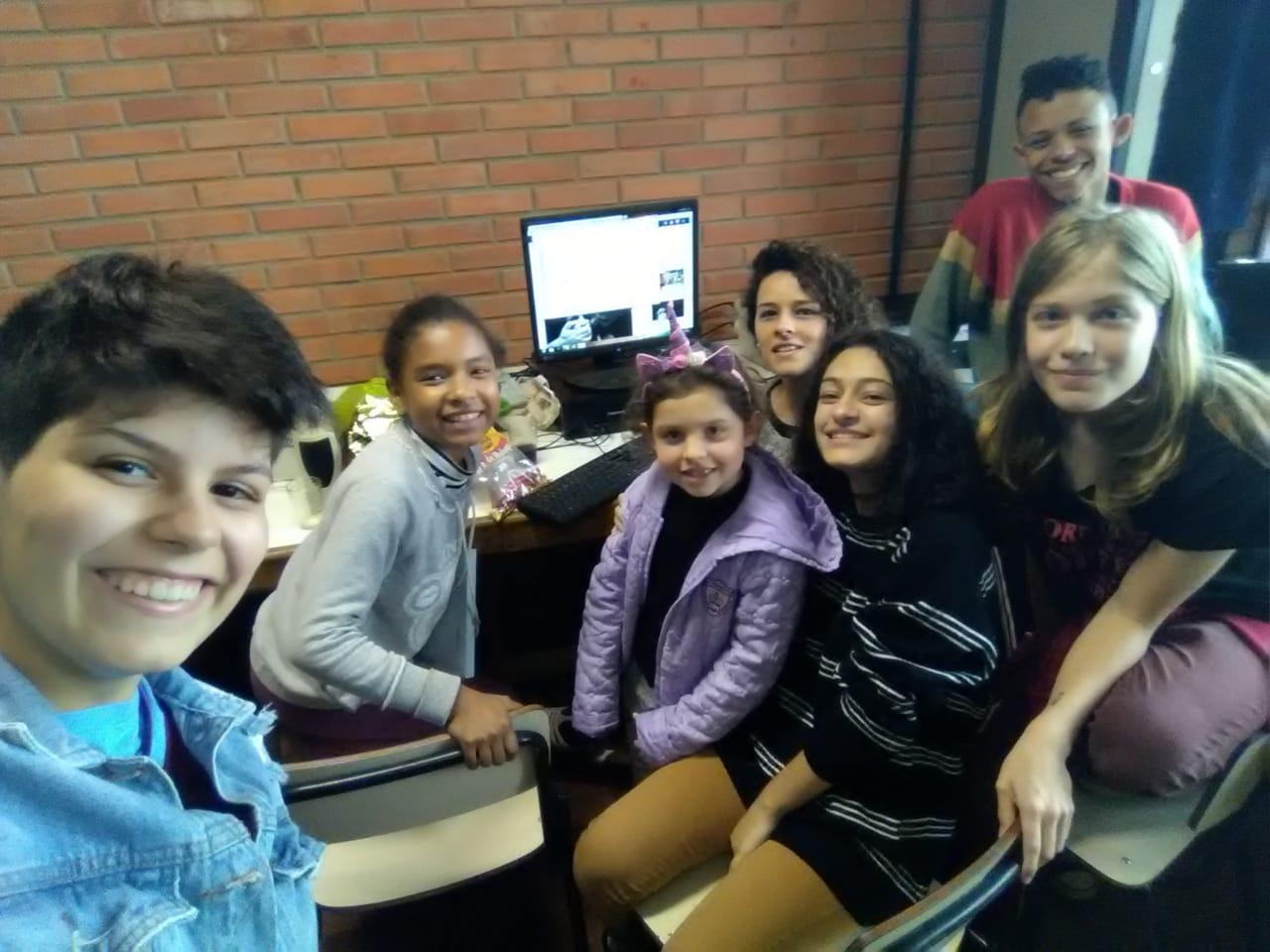 Foto com 5 estudantes e um professor ao fundo. Todos estão à frente de um computador e sorrindo para a câmera