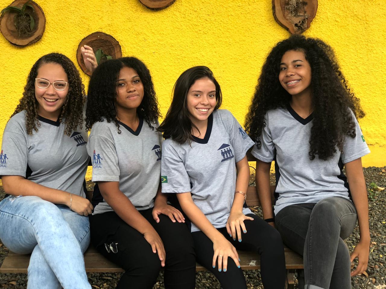 Foto de quatro adolescentes sentadas sorrindo para a foto. Elas usam uniforme escolar e ao fundo há uma parede amarela.