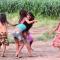 Foto de quatro crianças brincando em uma área externa com vegetação rasteira.
