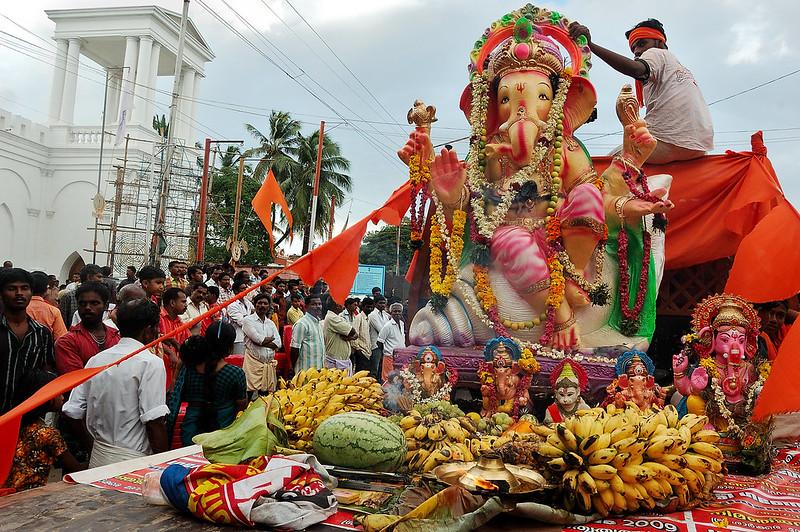 Foto de uma estátua da divindade Ganesha repleta de furtas e outros alimentos. Há pessoas em volta