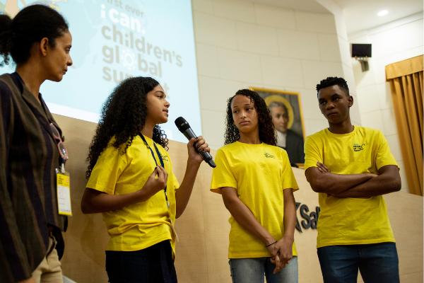 Foto de uma apresentação, em que hpa três adolescentes de camiseta amarela à direita e uma adulta à esquerda. Uma das adolescentes está com microfone na mão falando.