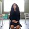 Foto de uma adolescente sentada em uma sala de aula com carteiras vazias. Há uma janela iluminada ao fundo, e a jovem veste um vestido preto e sorri para a câmera