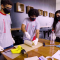 Grupo de estudantes confeccionando as placas em braile