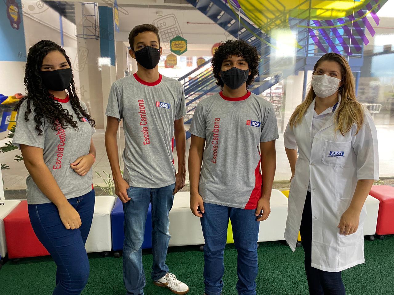 Três adolescentes, dois meninos e uma menina, e uma mulher adulta posam lado a lado. Os jovens usam uniforme escolar e a mulher usa jaleco branco. Todos estão de máscara.