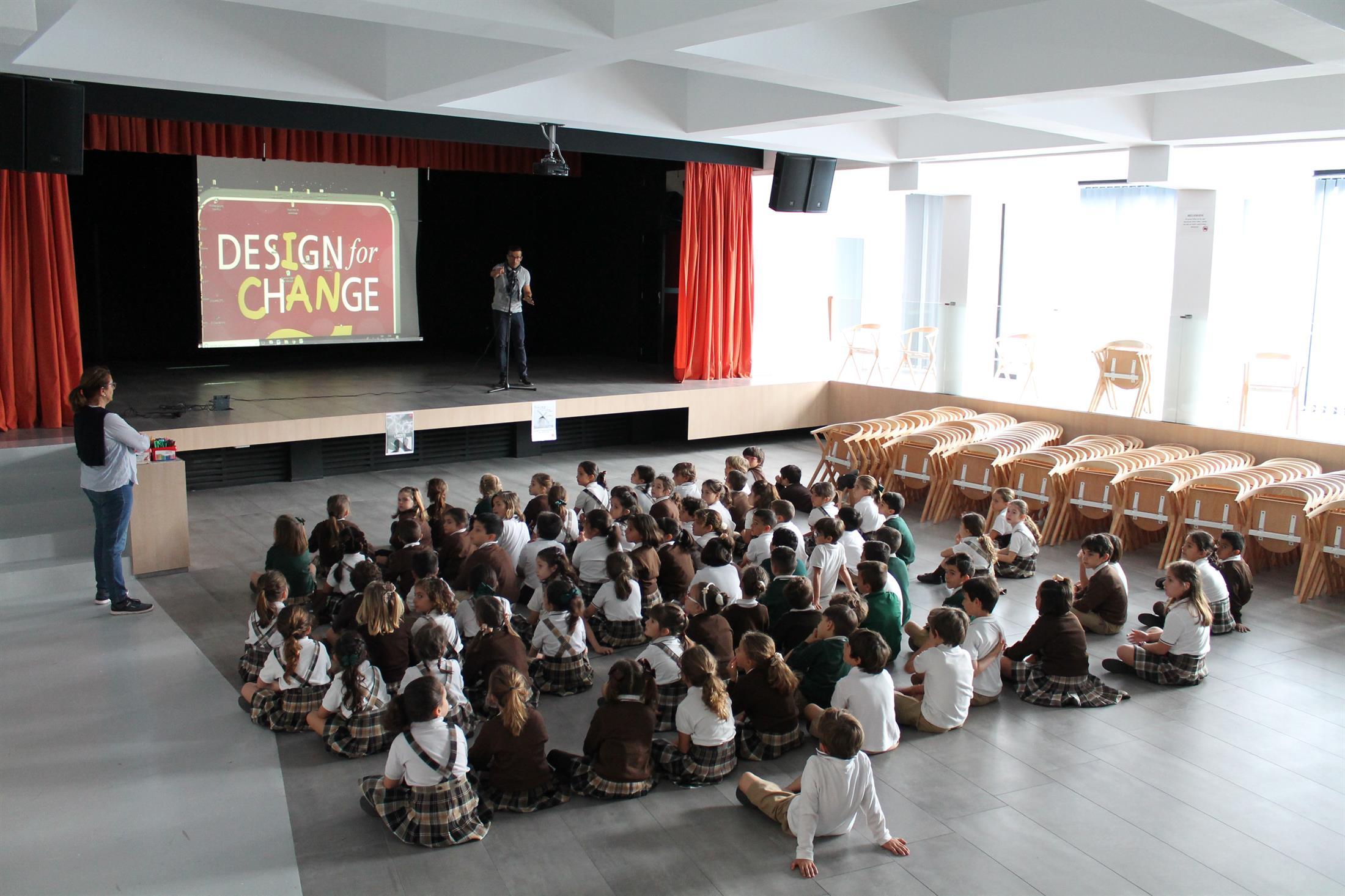 Foto de fundo de um salão, em que há crianças sentadas enfileiradas assistindo a um telão com o logo do Design For Change.