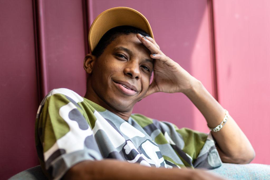Foto de um jovem negro que olha para a câmera com uma mão na cabeça. Ele usa boné para o lado e uma camiseta camuflada.