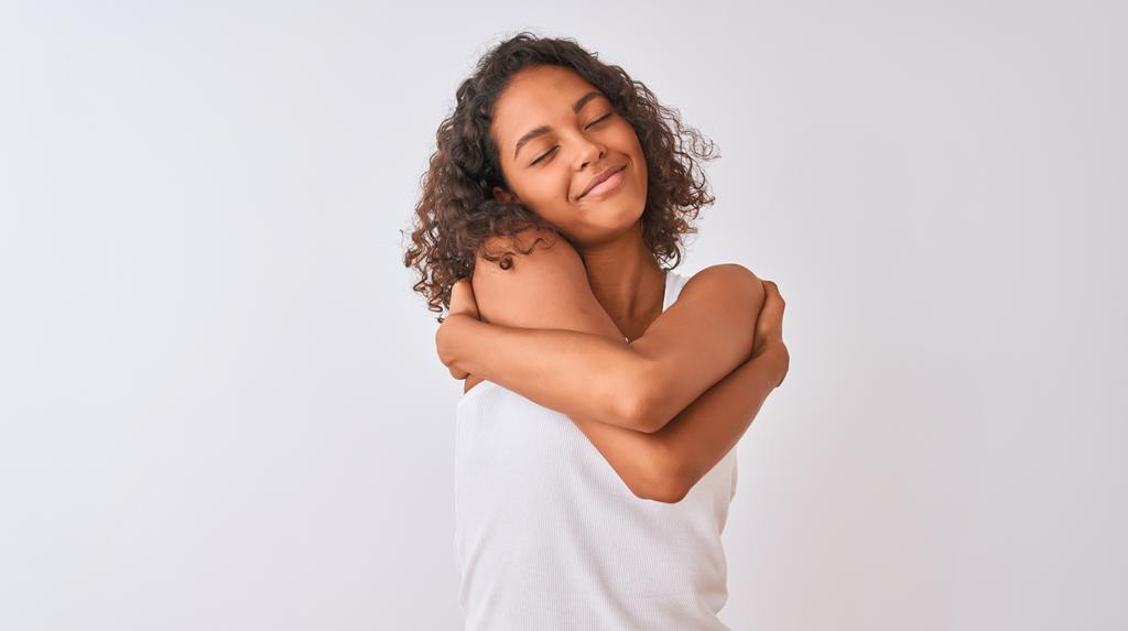 Foto em que uma jovem negra se abraça. Ela veste uma camiseta branca e está de olhos fechados e sorrindo.