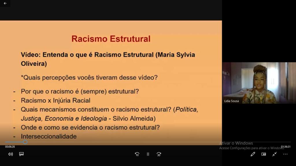 Print de uma chamada de vídeo. Um slide laranja sobre Racismo Estrutural ocupa mais que a metade da tela e ao lado há uma jovem negra falando.